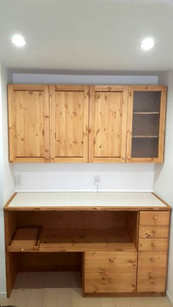 パイン材のキッチンカウンターとチェッカーガラスの吊戸棚